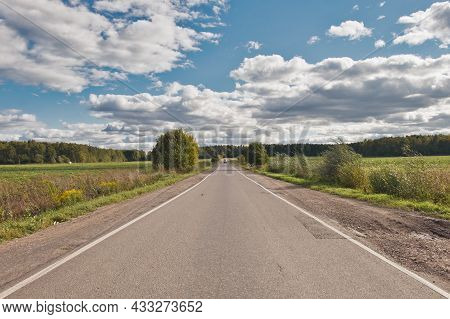Lanscape With Asphalt Automobile Road Through The Green Field And Clouds On Blue Sky In Summer Day.