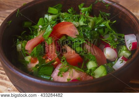 Vegetable Salad In A Clay Plate Of Tomatoes, Cucumbers, Radishes, Dill, Onions, Parsley On A Wooden