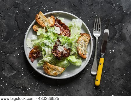 Caesar Salad With Bacon On A Dark Background, Top View. Delicious Brunch, Appetizer, Tapas