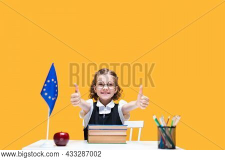 Happy Caucasian Schoolgirl Sitting At The Desk Gesturing Thumbs Up. English Lesson. Eu Flag