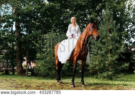 Happy Young Bride In White Wedding Dress And With Bouquet Sits Astride Brown Horse. Smiling Beautifu