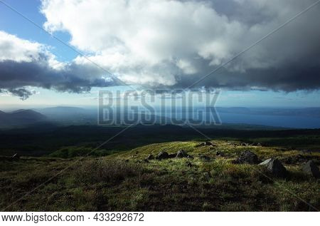 Nature landscape of Chile, Sun is shining on green grass on slope of Villarrica volcano, low clouds, Villarrica lake on horizon