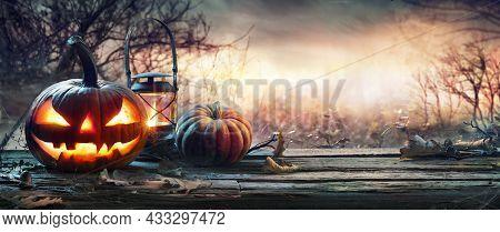 Halloween Pumpkin On Table In Spooky Landscape