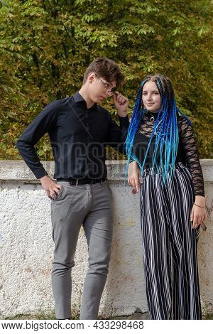 A Man Is Flirting With A Woman. A Couple Of Young People Are Standing At A High Concrete Parapet. Ye