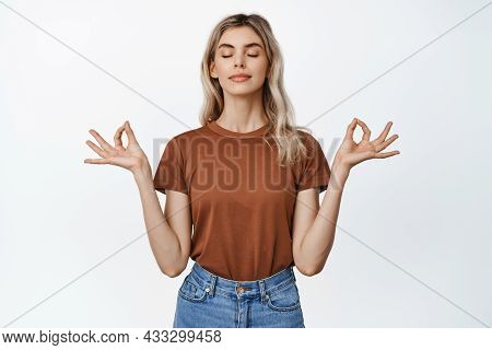 Young Relaxed Woman Close Eyes And Practice Yoga, Meditating With Peaceful Expression, Showing Mudra