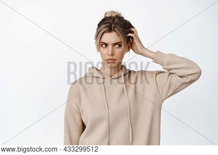 Questioned Girl Scratch Head, Touch Her Hair And Look Aside Puzzled, Stands Confused In Casual Cloth