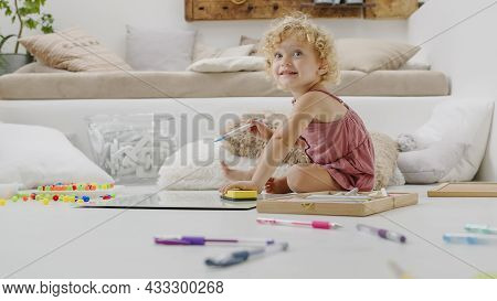 Smiling Child, Beautiful Little Girl With Blue Eyes And Curly Blonde Hair, Draws And Writes Cheerful