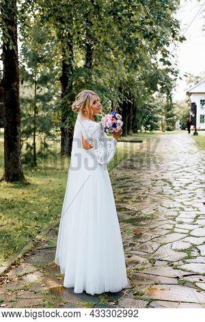 Profile Portrait Of Happy, Beautiful, Elegant Bride Posing In White Wedding Dress With Bouquet Of Fl