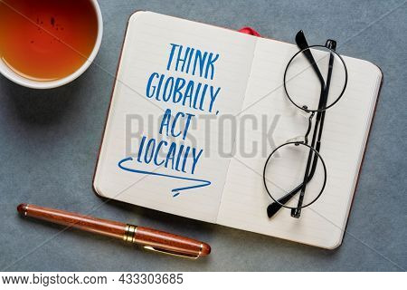 Think globally, act locally reminder - handwriting in a notebook or journal with a cup of tea, business, education and environment concept