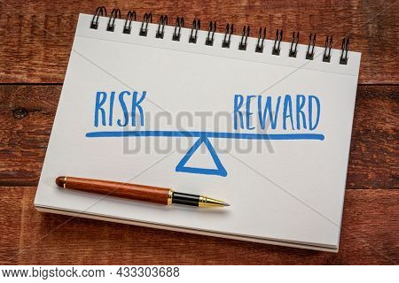 risk and reward balance concept, sketch in a spiral notebook with a stylish pen against weathered barn wood table