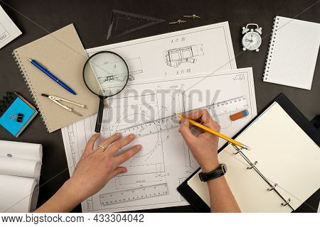 Mechanical Drawing On Sheets Of Paper. Hands On The Table Top View. Workflow Of An Architect, Engine