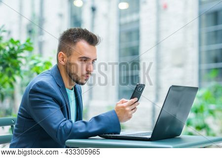Young successful caucasian businessman works in an outdoor cafe using a computer. Business, freelance and remote work.