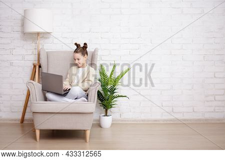 People, Technology, Internet And Online Education Concept - Cute Preteen Girl Sitting In Armchair An