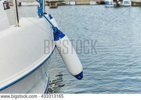 White Fenders Suspended Between A Boat And Dockside For Protection. Maritime Fenders