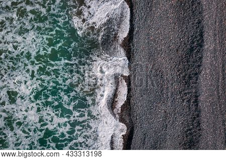 Green Stormy Waves With Sea Foam Breaking On Black Sand Beach, Sea Texture View Directly Above