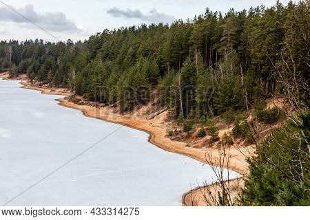 View From Up Of Hill To Frozen Lake And To Brown Coast Covered With Pine Trees And Birches. Early Sp