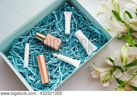Beauty Box With Samples And Miniatures Of Creams, Serum, Perfume, Lipstick And Foundation On Blue Pa