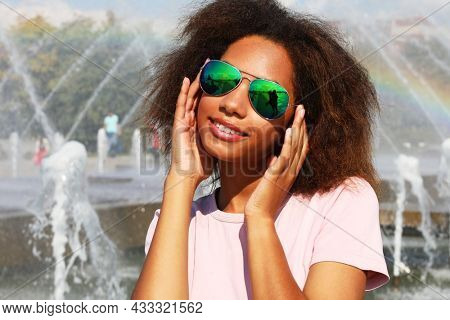 Young afro woman wearing sunglasses with perfect teeth and dark clean skin having rest outdoors
