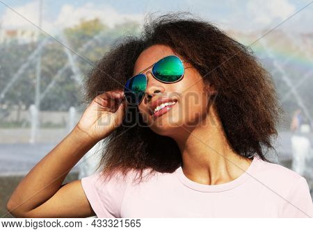 Young afro woman wearing sunglasses with perfect teeth and dark clean skin having rest outdoors, smiling after received good positive news.