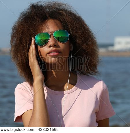 Young afro american woman in sunglasses listening to music in headphones on her mobile phone near sea.