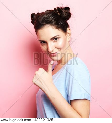 Young brunette woman in blue t-shirt smiles and raises her thumbs up over pink background.