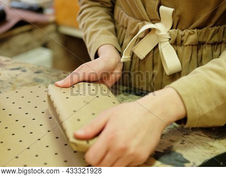 Lifestyle, freelance and home business concept: young woman folds packing box in sewing workshop