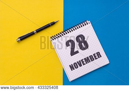 November 28th. Day 28 Of Month. Calendar Date. Notebook With A Spiral And Pen Lies On A Yellow-blue