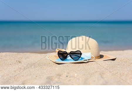 Vacation At Sea During A Virus Pandemic. Heart-shaped Sunglasses, Hat And Medical Mask On The Beach