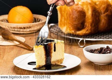 Using Metal Fork Taking A Bite Of Delicious Homemade Mango Cheesecake Topping With Chocolate In Whit