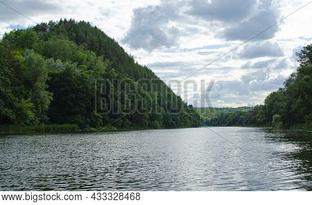 Summer In The River Valley: Contagious Greens Foliage Is Evening. Wooded Mountains Along The Banks O