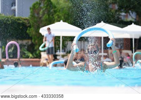 Young Woman Knocking Noodle On Water Of Swimming Pool On Aqua Aerobics
