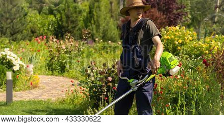 A Young Man In A Straw Hat Is Mowing A Lawn With A Lawn Mower In His Beautiful Green Floral Summer G