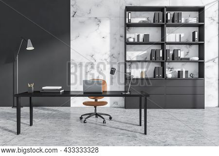 Close View On Office Room Interior With Laptop, Comfortable Armchair, Desk, Books, Folders, Bookshel