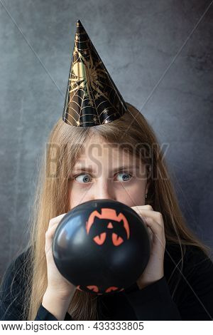 A Teenager Girl In A Halloween Paper Cap Inflating Black Ball For Halloween. People, Halloween, Deco