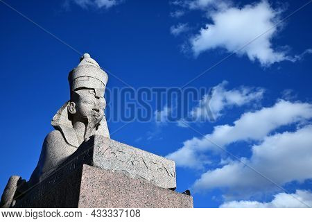 Granite Sphinx From The Ancient Thebes In St. Petersburg On The Background Of A Blue Sky With White