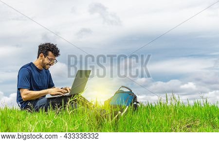 Young Man In Glasses Working On His Laptop, Man In The Field With His Computer