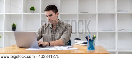 Young Businessman Sitting In The Office With A Laptop, Typing Messages With Partners Through Chat, H