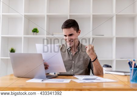 Young Businessman Sits In His Office With A Laptop, He Looks Delighted As He Reads The Documents Tha