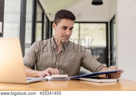 A Young Businessman Sitting In The Office With A Laptop, Is Pressing A Calculator To Calculate The B