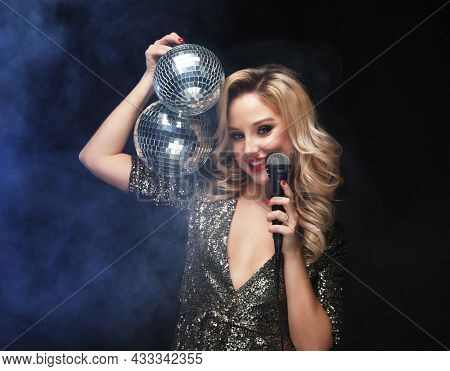 Portrait of elegant young woman with microphone and disco balls at celebration New Year.
