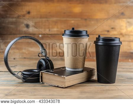 old book with headphone and a cup of coffee in a disposable paper cup on a wooden table. Remote education concept.