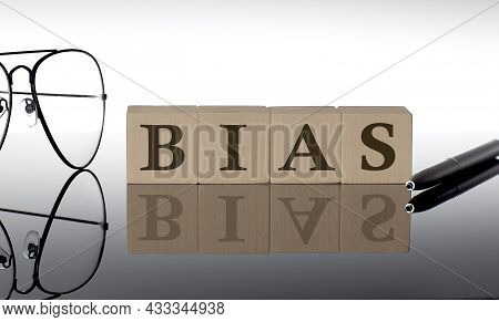Close-up Of Bias Wooden Blocks On Black Background With Glasses And Pen