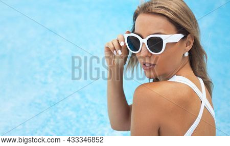 Close-up Portrait Of Beautiful Blonde Woman 25-30 Years Old Is Resting At The Pool In A White One-pi
