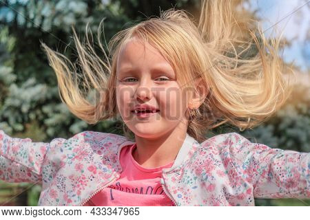 Portrait Of A Child, Cheerful Beautiful Girl, Blonde, 6 Years Old With Blond Long Tousled Hair, In T