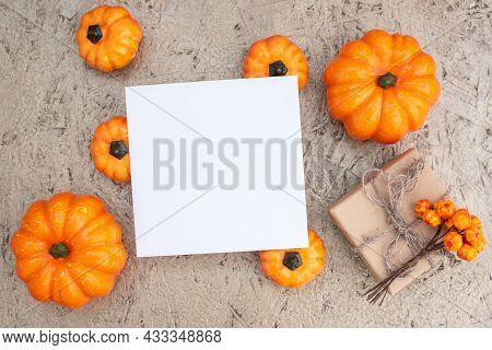 Small Orange Pumpkins Gift Box With Berries And Blank Paper Card On Plywood Background Upper View. A