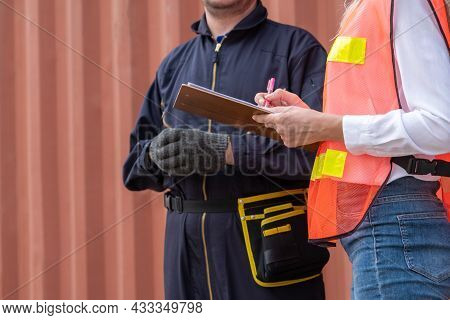 Industrial Worker Works With Co-worker At Overseas Shipping Container Yard . Logistics Supply Chain