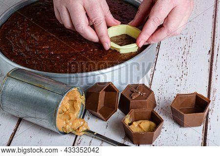 Confectioner Cutting A Piece Of Brazilian Honey Cake To Place In A Chocolate Mold Filled With Dulce