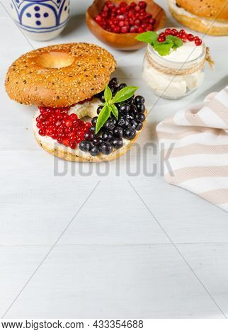 A Healthy Natural Delicacy. Bagel With Cream Cheese And Fresh Wild Berries. A Sweet Sandwich. Vertic