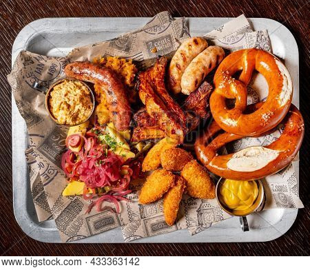 Oktoberfest beer menu germany traditional rustic style, veal pretzel, sausage with mustard in white plate on wooden rustic table.