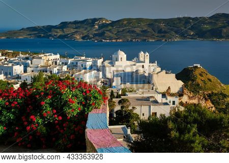 Picturesque scenic view of Greek town Plaka on Milos island over red geranium flowers and Orthodox greek church. Plaka village, Milos island, Greece. Focus on buildings
